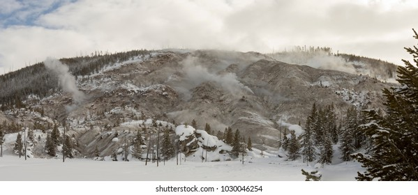 Panoramic landscape of snow covered field against Roaring Mountain with active geyser steam vents with pine trees against blue skies in Yellowstone National Park, Wyoming in winter.