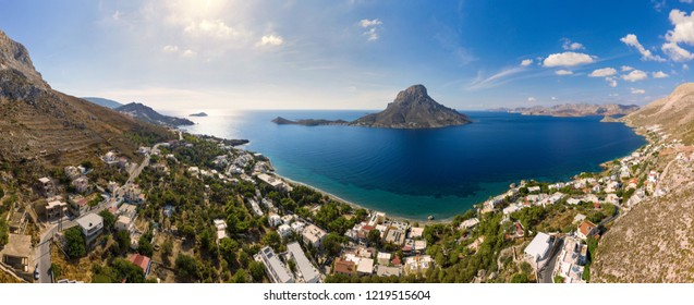 Panoramic landscape of Telendos island in distance and part of Kalymnos island, Massouri, at sunset, Greece, bird's eye view