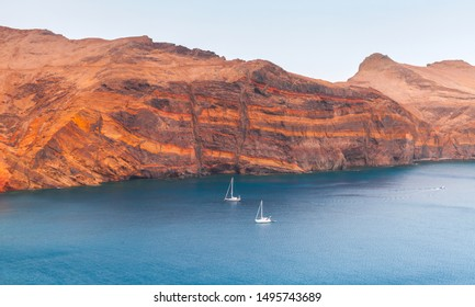 Panoramic landscape with two yachts going near red coastal rocks of Ponta de Sao Lourenco, Madeira island, Portugal