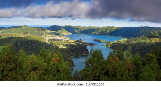 Panoramic landscape view of green and blue crater lakes of Lagoa Azul and Lagoa Verde and Sete Cidades village in the crater of dormant volcanoes, on Sao Miguel island, Azores, Portugal.
