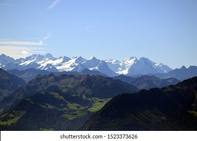 Panoramic landscape view of meadows, mountain ranges and snowy mountain peaks from the top of Rigi Kulm, Mount Rigi in Switzerland