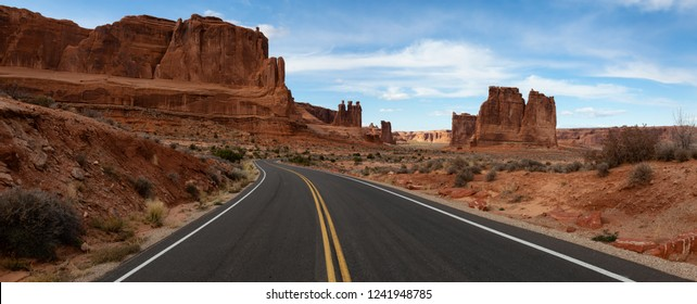 Panoramic landscape view of a Scenic road in the red rock canyons during a vibrant sunny day. Taken in Arches National Park, located near Moab, Utah, United States.