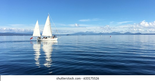 Panoramic landscape view of a white yacht sail boats sailing over Lake Taupo in the North Island of New Zealand.