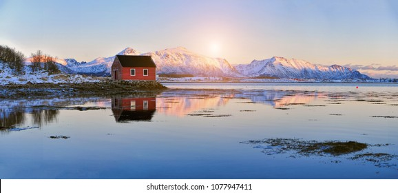 Panoramic landscape - winter mountains and fjord with rorbu - typical red fishing lodge. Reflection in water. Norway. The Lofoten Islands.