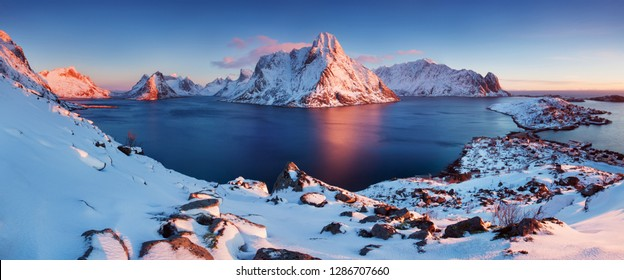 Panoramic landscape, winter mountains and fjord reflection in water. Norway, the Lofoten Islands. Colorful winter sunset or sunrise above the arctic circle.
