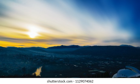 A panoramic long exposure view of a cloudy sunset over a small, hazy town