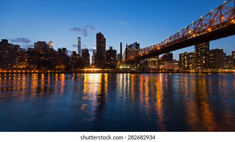 Panoramic midtown Manhattan skyline with reflections at night from Roosevelt island. New York City.