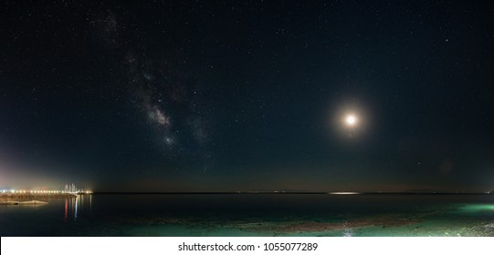 Panoramic Milky Way galaxy and young moonset. Milky Way galaxy over the seacoast with moonset, small harbor on the left side. The night sky is astronomically accurate.