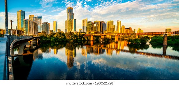 Panoramic mirrored town lake reflections of Austin Texas golden hour sunset downtown skyline cityscape across Colorado river perfect symmetry during calm afternoon sunset panorama city view