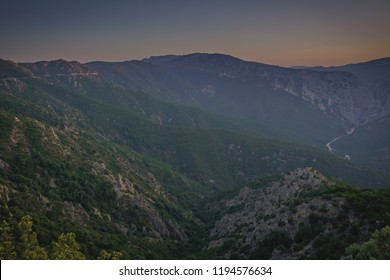Panoramic Mountain Landscape view during a beautiful sunset, with layered blue mountains and river, Sardinia, Orosei region.