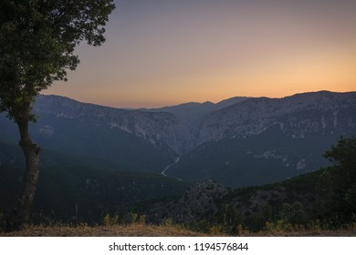 Panoramic Mountain Landscape view during a beautiful sunset, with layered blue mountains and tree in foreground, Sardinia, Orosei region.