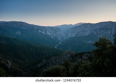 Panoramic Mountain Landscape view at dusk, with layered blue mountains and river, Sardinia, Orosei region.