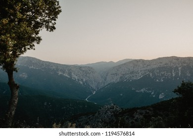 Panoramic Mountain Landscape view at dusk, with layered  mountains and one tree in foreground, Sardinia, Orosei region. Vintage  Film effect with grain.
