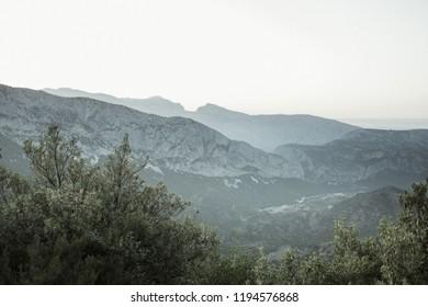 Panoramic Mountain Landscape view at dusk, with layered  mountains, Sardinia, Orosei region. Vintage  Film effect with grain.