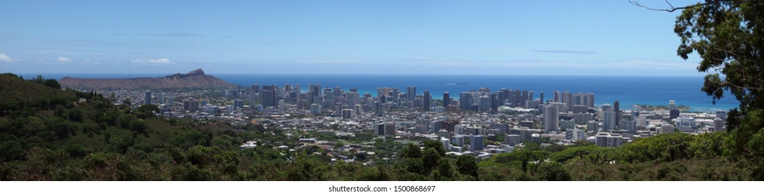 Panoramic Mountain view of Honolulu, Diamond Head, Waikiki, Buildings, parks, hotels and Condos with Pacific Ocean stretching into the distance on nice day.