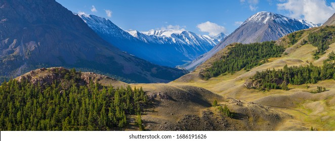 Panoramic mountain view, morning light. Steep slopes, snowy peaks and forest. Traveling in the mountains, trekking.