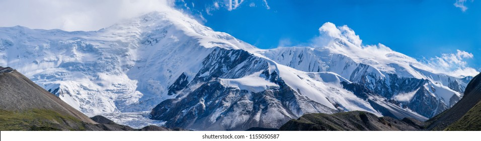 The panoramic mountain view with rocks and ice in Tian Shan mountains in Central Asia near Almaty covered by clouds. Best place for active life, climbing, hiking and trekking in Kazakhstan.