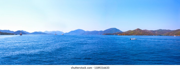 Panoramic nautical seascape. Calm sea, boats, green islands with hills and pale blue mountains on the horizon, clear sky. Background. Mediterranean, Turkey