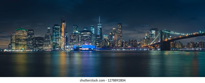 Panoramic night photography, of the Manhattan skyline and Brooklyn Bridge, in New York, USA, from the Dumbo area, in Brooklyn