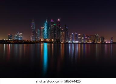 Vista panorámica nocturna de los rascacielos de Dubai Marina y sus reflejos en la bahía