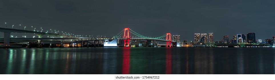 Panoramic nightview of Rainbow Bridge illuminated in red as a sign of Tokyo Alert, coronavirus alert for Tokyo area, in Odaiba Japan.