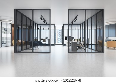 Panoramic office interior with glass walls, a concrete floor and rows of tables with computers on them. 3d rendering mock up