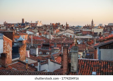 Panoramic overlooking view over the tiled roofs of the old traditional houses of the historic centre of Toulouse, France, dominated by the bell towers of Jacobins Convent and Saint-Sernin Basilica