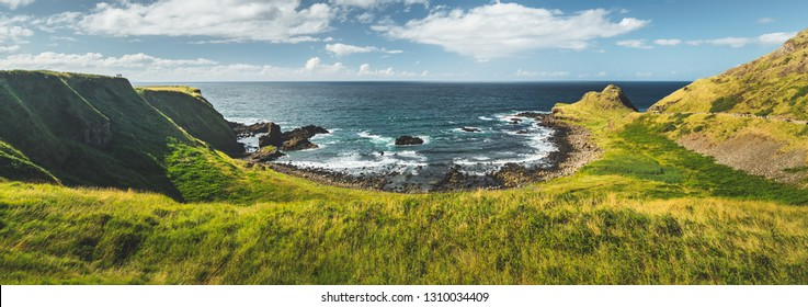 Panoramic overview of the Northern Ireland shoreline. Amazing Irish landscape. Green grass covered shore surrounded by the ocean water. Cozy bay under the cloudy sky background. Wilderness.