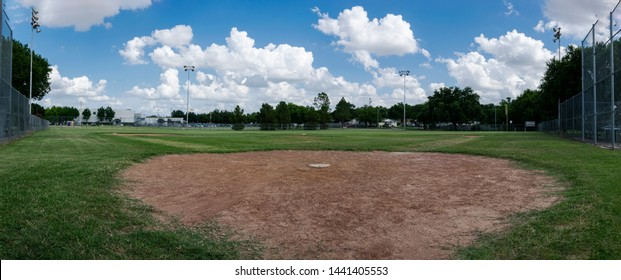 A panoramic photo of a baseball field looking from behind home plate out across pitcher's mound and the diamond to outfield wiht fluffy clouds in the blue sky overhead.