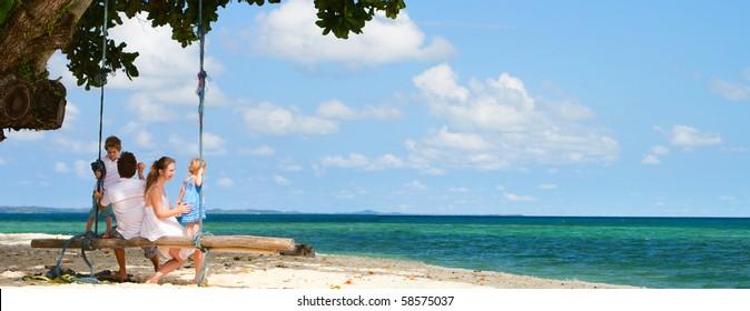 Panoramic photo of family of four having fun on tropical beach