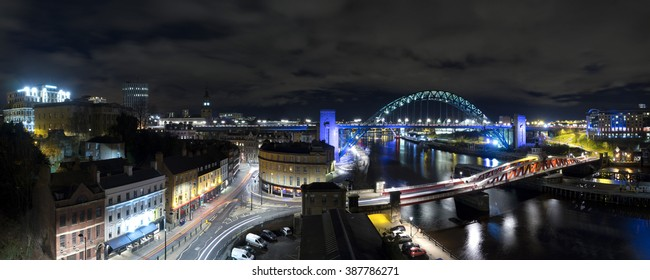 Panoramic photo of the Quayside in Newcastle upon Tyne and Gateshead, taken at night. Several of the Tyne's bridges are in view, as well as many of the historic buildings on the Quayside.