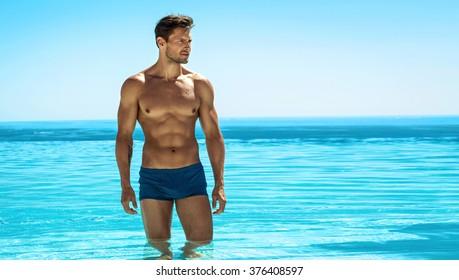 Panoramic photo of sexy man posing in swimming pool