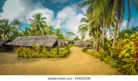 Panoramic photo of simple houses with straw roofs and surrounding palms and other plants in Will-will, Nuku, Papua New Guinea.