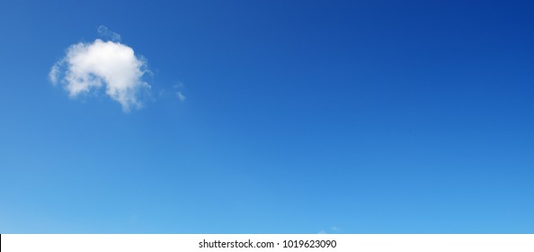 Panoramic photo with small cloud on bright blue sky background. Free space for text.