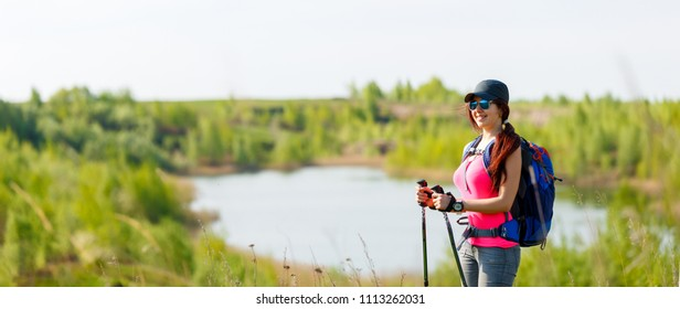 Panoramic photo of sporty woman with walking sticks on background of lake and green vegetation