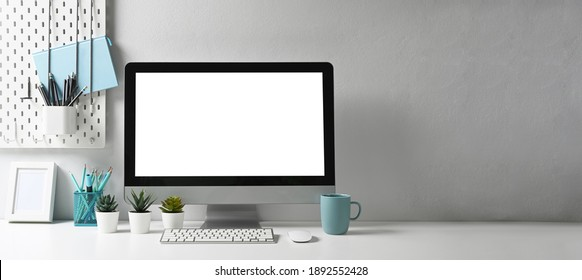 Panoramic photo of stylish workspace with mock up computer and office supplies gadget. Blank screen and copy space for graphic display montage.