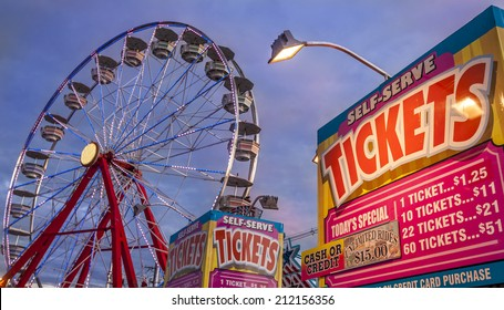 Panoramic photo of ticket sale booth in a theme park with a ferris weheel on the background at sunset.