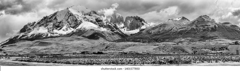 Panoramic photo of Torres del Paine peaks coming from clouds. Torres del Paine national park, Chile. Black and white