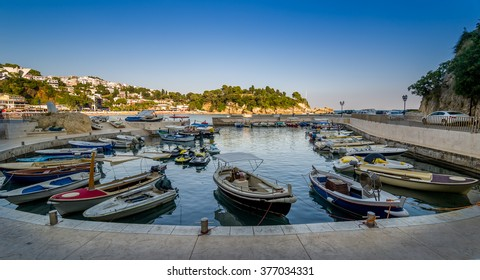 Panoramic photo of traditional fishing boats pier at calm summer evening. Ulcinj, Montenegro.