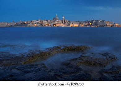 Panoramic photo of Valletta, capital city of Malta in dusk. Seafront skyline view as seen from Sliema, Malta. Illuminated historical buildings after sunset.