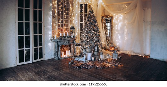 panoramic photo warm, cozy evening in Christmas room interior design,Xmas tree decorated by lights presents gifts toys, candles, lanterns, garland lighting indoors fireplace.holiday living room.New