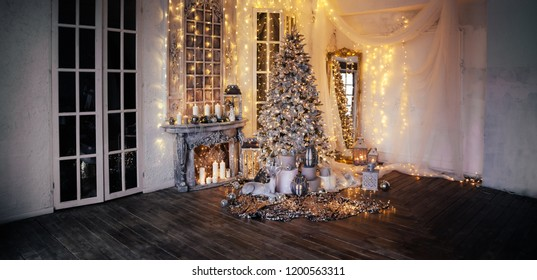 panoramic photo of warm cozy evening in Christmas room interior design,Xmas tree decorated by lights gifts,toys, deer,candles, lanterns, garland lighting indoors fireplace.holiday.magic New year