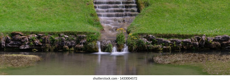 Panoramic photo of a waterfall flowing down stairs in an ornamental garden