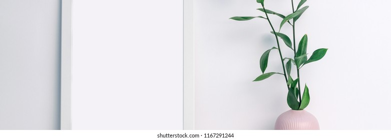 Panoramic photo of a white frame mockup with a pink notched vase with twigs with green leaves on an empty white background