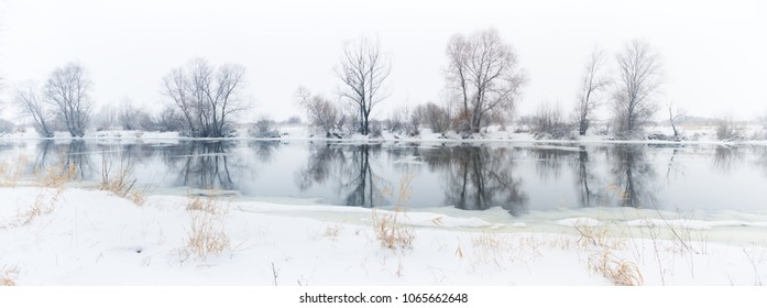panoramic photo of a winter river with snowy banks and ice.