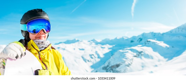 Panoramic photo of woman in helmet and with snowboard in background of snowy landscape