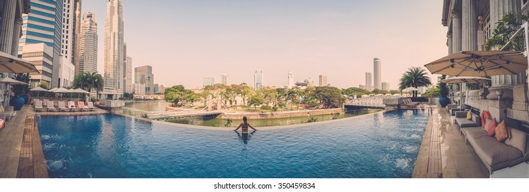 Panoramic photo of woman relaxing at luxurious high rise swimming pool.
