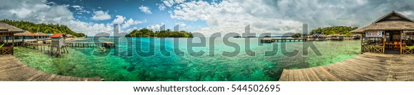 Panoramic photo of wooden jetty with wooden beach bar and clear blue sea in Katupat in Sulawesi, Indonesia.