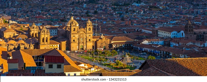 Panoramic photograph of the ancient inca capital city Cusco at sunset with its Plaza de Armas main square, cathedral and Compania de Jesus Jesuit church, Peru.