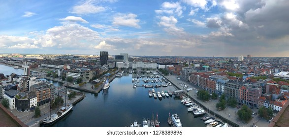 Panoramic picture of the city of Antwerp with the view of the an unnamed pier and many boats and gloomy clouds in the background.